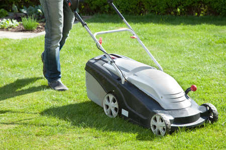 Outdoor shot of a man mowing the lawn