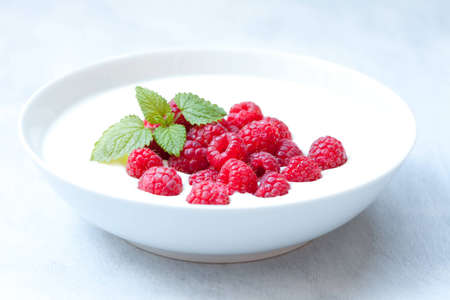 Bowl of yogurt with some fresh raspberries and mint on top Stock Photo