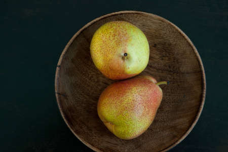 Top-view of a pair of pears in a wooden bowl