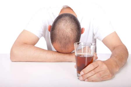 El hombre con su cabeza sobre la mesa la celebraci�n de una bebida alcoh�lica en la mano