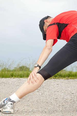 Male runner strechting after a run