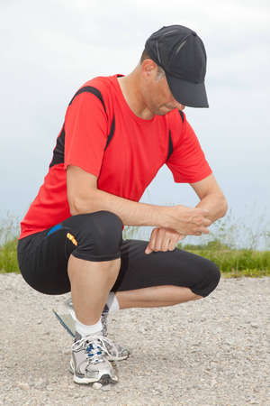 A runner checking his stopwatch after finishing his run