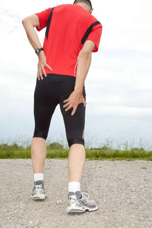 calf pain: A runner holding his thigh Stock Photo