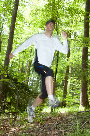 Trail runner running at a fast pace through the woods