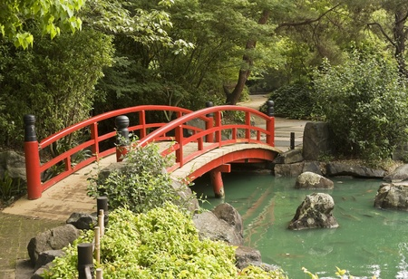 A red wooden bridge over a pond in a Japanese garden photo