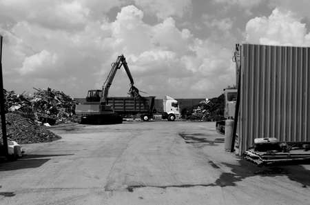 Black and white photo of a truckload of recyclables on a truck