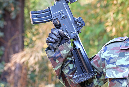 bb: A man in soldier suit with BB gun
