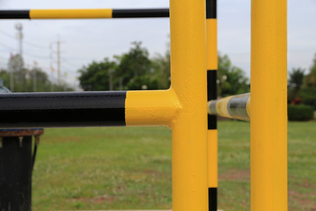 Yellow and black iron fence around small groundwater pump,protection