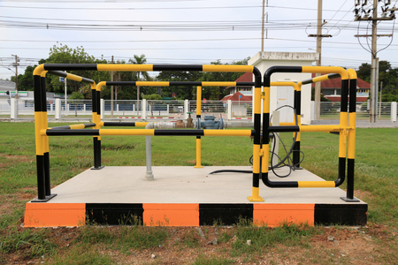 groundwater: Yellow and black iron fence around small groundwater pump,protection