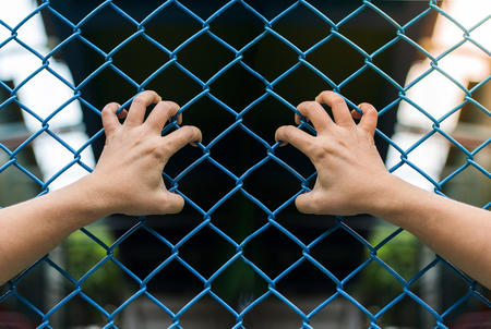 freedom concept: Girl hands on the wire fence,freedom concept