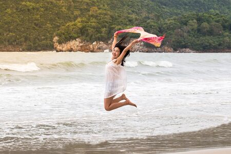 Beautiful woman with scarf jumping happy on the beach with mountain background