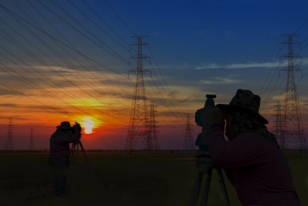 Silhouette man working survey on electric tower pole construction building in sunrise sky