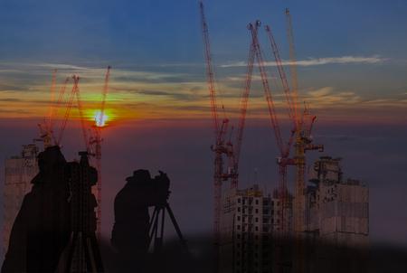 Silhouette man working survey on tower crain construction building in sunrise sky