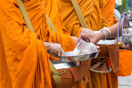 Boeddhistische monnik van Thailand, terwijl ze op een rij staan, wachten dat mensen rijst en voedselaanbod in hun aalmoespot zetten om merit te maken