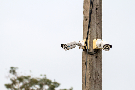 Two cctv camera on electric pole watches down below important events Stock Photo