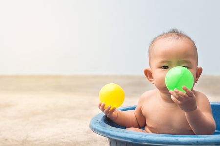 Cute New Born Baby playing ball in the plastic basin during shower,children learning Stock Photo