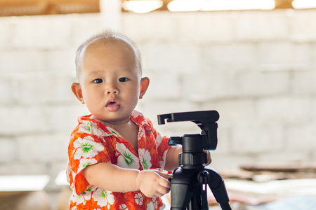 Cute New Born Baby playing with tripod,children learning