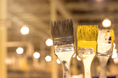 Old Paint brush used resting on paint background for design,selective focus under yellow light Stock Photo