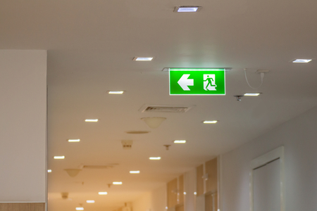 green emergency exit sign in hospital showing the way to escape