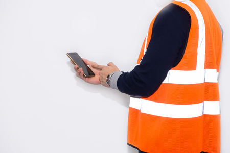 Asian engineer wearing safety helmet and safety glasses holding smartphone on white background