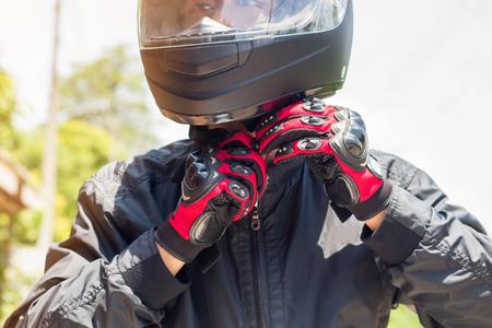 Mann in einem Motorrad mit Helm und Handschuhen ist eine wichtige Schutzkleidung für Motorrad-Drosselklappensteuerung, Sicherheitskonzept Standard-Bild