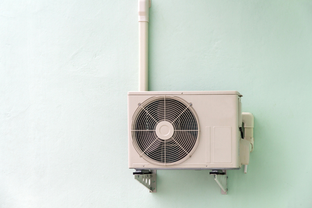 Air compressor on wall pedestal with siding factory wall background.