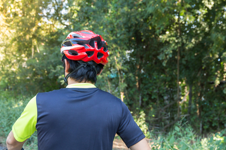 Man with helmet glove for safety riding a bicycle at countryside road along a forest,Cross country riding,cycling activity and sports. Banque d'images