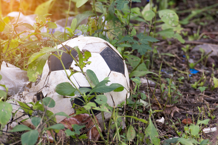 Abandoned old football or soccer ball in the field grass not available