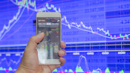 business hand hold and touch screen on smartphone or cellphone over blur stock chart market monitor background,business stock concept 写真素材