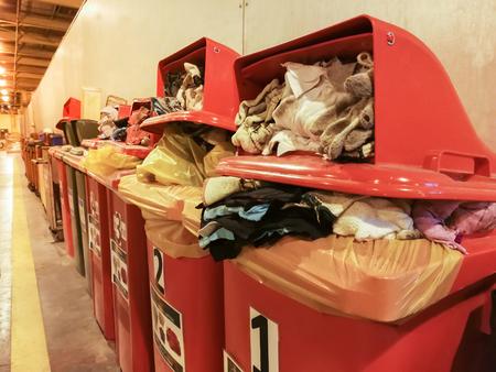 Cotone usato di stracci e guanti contaminato con olio ordinato in un bidone della spazzatura rosso in fabbrica, contenitori per rifiuti rossi pieniFu