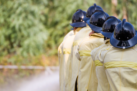 Firemen using water from hose for fire fighting at fire fight training of insurance group.Firefighter wearing a fire suit for safety under the danger training case.