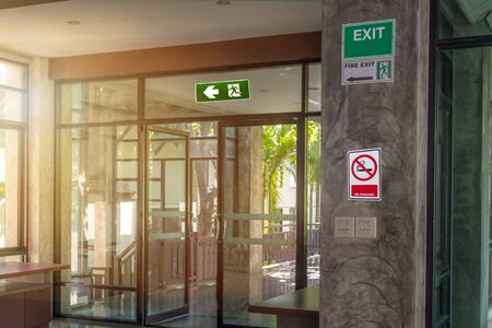 Green emergency exit sign and label no smoke in rest corner showing the way to escape and caution safety awareness