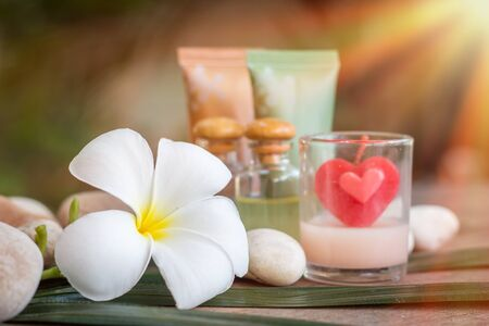 Aromatherapy product spa of therapy massage with plumeria or frangipani flowers, stones, aroma candle and oil on the desk,Spa treatment and skincare concept.