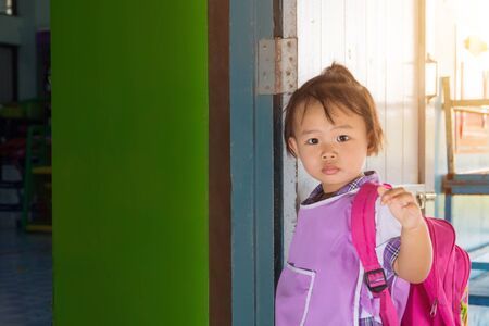 Asian preschool little girl student in general uniform and red bag going to school, back to school concept