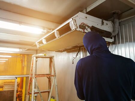 Male technician checking and fixing air conditioner indoors,maintenance and repair