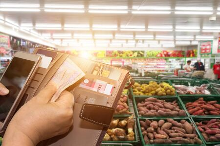 Beautiful Asian woman in supermarket shopping with credit card and cardholders borrow funds with which to pay for goods and services Stockfoto