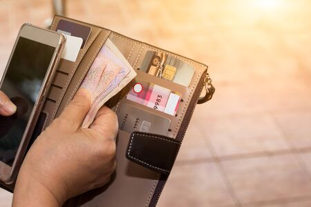 Cropped shot view of female hands picking credit cards from her wallet Stockfoto