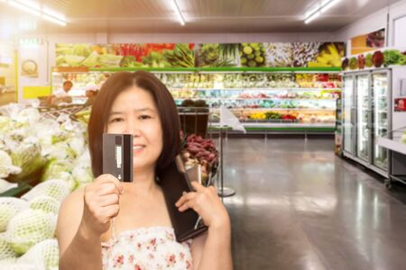 Beautiful Asian woman in supermarket shopping with credit card and cardholders borrow funds with which to pay for goods and services Stock Photo