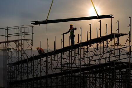 Man working on construction site with scaffold and building with sunset background, scaffolding for construction factory