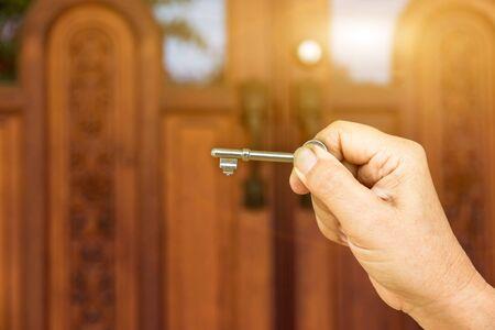 Key on hand of people open the door to inside, outside door open putting into front door Stockfoto