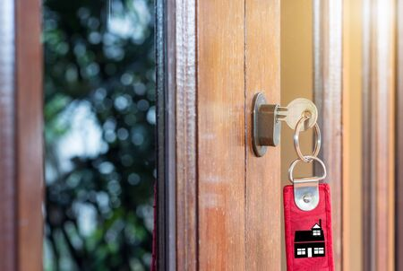 Key on hand of people open the door to inside outside door open putting into front door