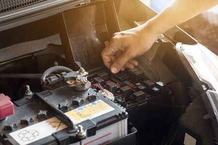 Auto mechanic working check system water and fill an old car engine at service station,change and repair before drive