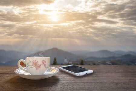 A cup of hot espresso coffee mugs placed with smartphone on a wooden floor with morning fog and moutains with sunlight background,coffee morning