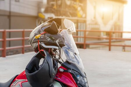 Motorcycle gloves and safety helmet hanging on a front seat of sport motorbike for safety