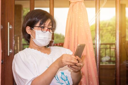 Asian women wear surgical mask are stay at home about disease virus covid-19 prevention