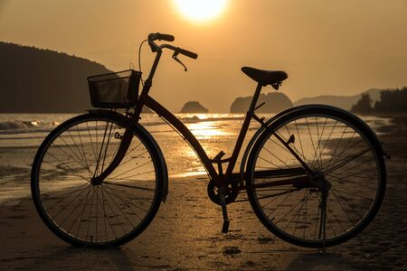 silhouette of bicycle at beach, bicycles on beach sunset or sunrise Stockfoto
