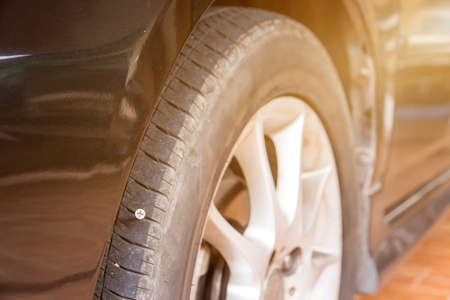close up of screw nail puncturing car tire Stock Photo