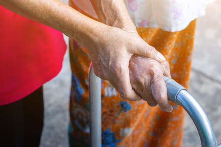 Asian old woman standing with her hands on a walker with daughter's hand,Hand of old woman holding a staff cane for helping walking Banque d'images