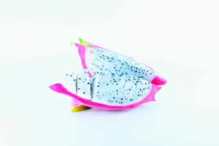 Dragon fruit is cut into pieces, revealing white flesh inside.