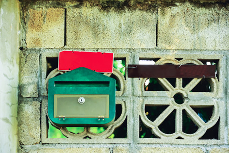 installed: Postbox red and green plastic sheets are installed in the wall of cement.